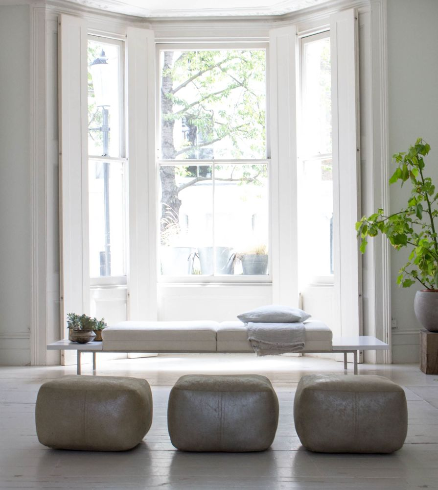 Serene white and minimal living room with leather pouf ottomans in a London home flooded with natural light - Atlanta Bartlett.